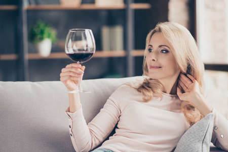 Portrait of pretty, charming, attractive, stylish connoisseur woman sitting on couch having raised glass with red wine in hand, examine, taste beverage Stock Photo