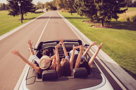 High angle shot of dreamy ladies and guy driver, chics girlfriends in headwear express emotions, success, euphoria, wind. Relax chill destination, vehicle rent, speed ride, students lifestyle Stockfoto - 95428270