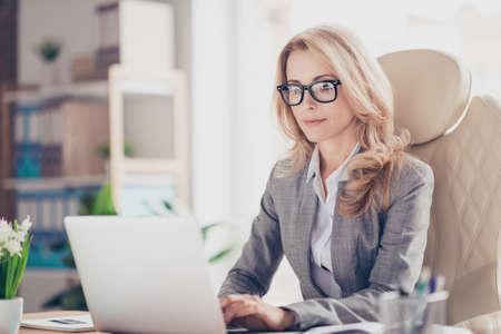 Hübsche, charmante, blonde Frau mit, Surfen, Tippen, Suchen, Arbeiten, Online-Expertise am Computer, Sitzen am Desktop in der Workstation, mit WiFi-Internet