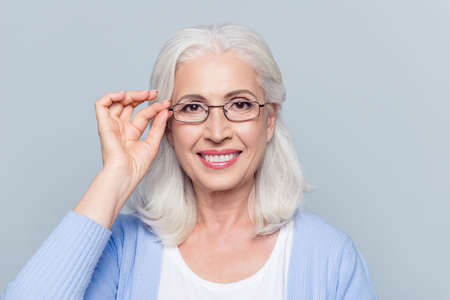 Close up portrait of stylish, aged, charming happy woman holding eyelet of glasses on face over grey background