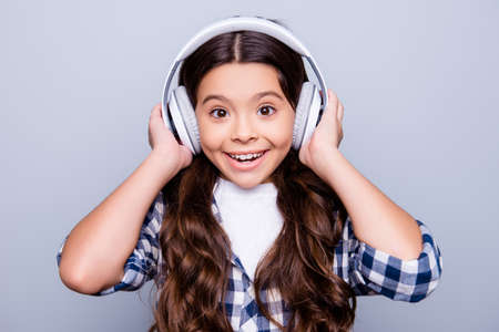 Close up portrait of happy joyful, cute, shocked kid holding earphones on her head with wide open eyes and mouth listening music standing over grey background