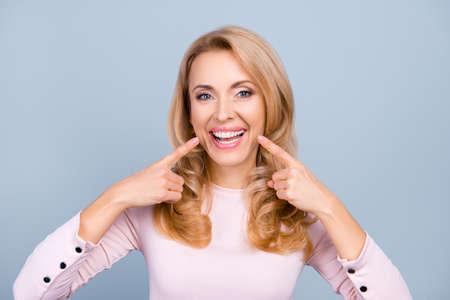 Mujer bonita y moderna en traje casual apuntando con dos dedos índice a su radiante sonrisa saludable sobre fondo gris Foto de archivo