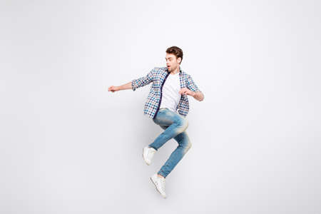 Mid-air shot of mad, crazy, cheerful, successful guy with bristle jumping, looking to the side, posing, gesturing against white background