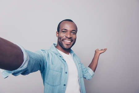 Close up portrait of excited cheerful glad with toothy smile dressed in denim casual jeans shirt demonstrating his new purchase isolated on gray background
