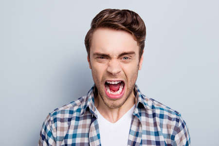 Aggressive man in checkered shirt with wide open mouth is out of himself, yelling, screaming, shouting with cruelty over grey background 写真素材