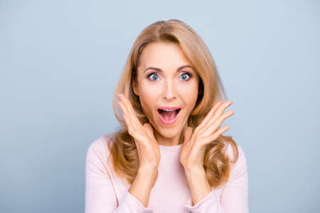 Charming, funny, pretty, comic, attractive, shocked woman with open mouth, screaming, shouting, yelling over grey background, holding palms near cheeks