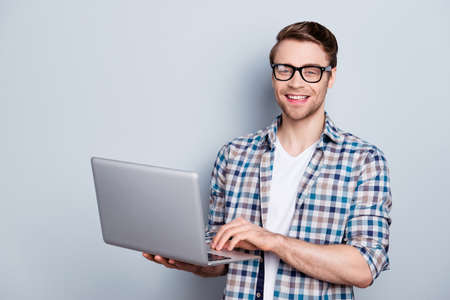Portrait of bearded, cheerful, brunet guy holding open laptop, looking at camera, searching information through wifi internet
