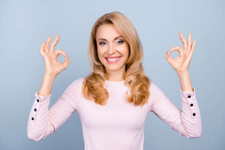 Portrait of pretty, charming, glad, nice woman with beaming smile showing two raised okay signs with fingers, isolated on grey background