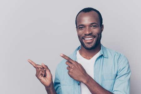 セクシーな、鮮やかな、2人の人差し指を指し示す輝く笑顔を持つ美しい男が空間をコピーし、カメラを見て、灰色の背景に隔離された肖像画 写真素材