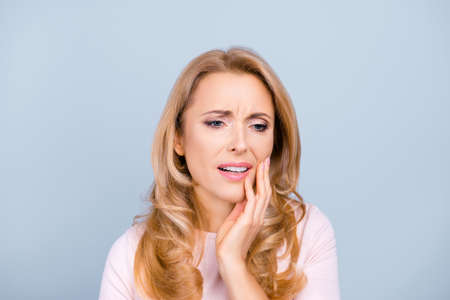 Portrait of beautiful, young, woman suffering from terrible strong teeth pain, touching cheek with hand over grey background, tooth pain, dentistry, dental care, health concept