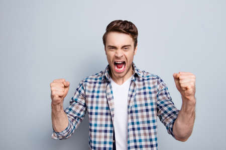 Aggressive man in checkered shirt with raised fists and open mouth is out of himself, yelling, screaming, shouting with cruelty over grey background 스톡 콘텐츠