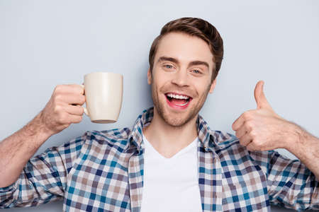 Close up portrait of cheerful, happy, smiling guy in checkered shirt, showing cup of coffee and thumb up over grey background, having rest, time-out, break