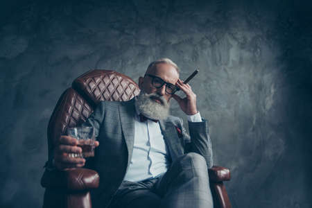 Minded, ponder, dreamy gentlemen, selective, bearded investor in glasses, hold cigarette and glass with cognac, in tux