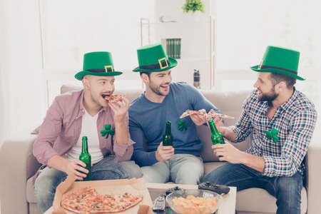 Portrait of stylish, handsome, attractive guys holding pieces of pizza in hands, speaking, laughing, drinking lager beverage, enjoying time together in Ireland
