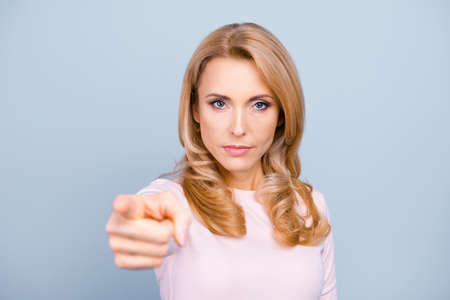 You annoy me! Close up portrait of serious strict aggressive nervous stressed woman pointing on camera isolated on gray background