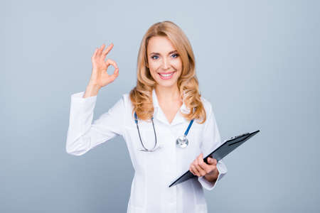 Portrait of confident experienced qualified happy smiling doctor holding clipboard with documents and showing okay sign, isolated on grey background