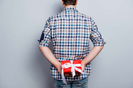 Backside view of man prepared red gift box with white ribbon on holiday and special occasion, isolated on grey background, hiding present behind his back, making surprise