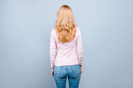 背中の背面図写真は、灰色の背景に隔離された、静かでカジュアルな服を着た美しい成功したプロの写真 写真素材