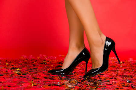 Close up cropped photo of stylish shiny elegant ideal perfect charming beautiful trendy black womans shoes isolated on red background floor covered with confetti