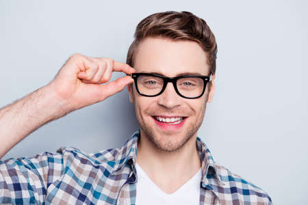 Portrait  of smart, clever, happy, positive guy holding eyelet of glasses on face looking at camera over grey background