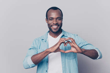 Portrait of creative, romantic, positive, cheerful, confident guy making love symbol, heart figure with fingers, looking at camera, isolated on grey background Stock Photo