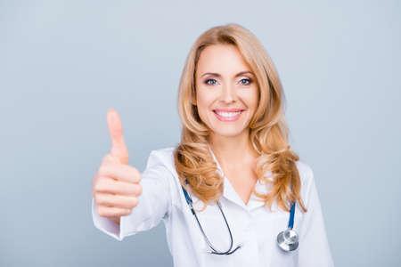 Feliz, bonita, atractiva, trabajadora médica de mediana edad en bata blanca mostrando el pulgar hacia la cámara sobre fondo gris Foto de archivo