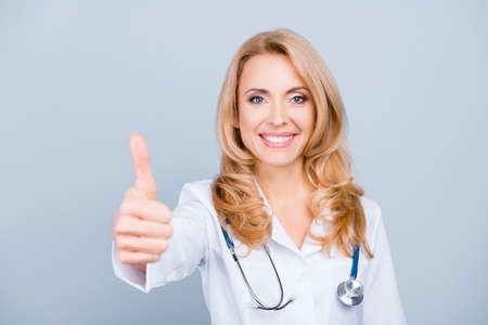 Happy, pretty, attractive, middle age medic worker in white coat showing thumb up to the camera over grey background