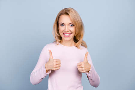 Portrait of pretty, charming, glad, nice woman with beaming smile showing two thumbs up sign with hands, isolated on grey background Stock Photo