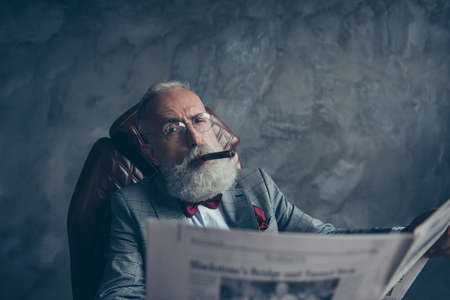 Handsome, attractive rich old man in glasses with cigarette in mouth, hold newspaper, looking at camera with one close eye