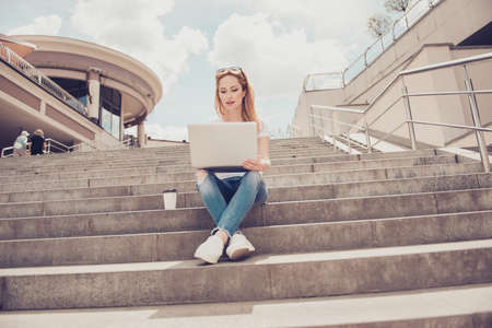Pretty lady using modern netbook writing article
