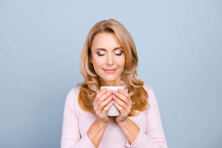 Close up portrait of satisfied pretty peaceful delightful calm woman is smelling aromatic cacao isolated on gray background Stockfoto