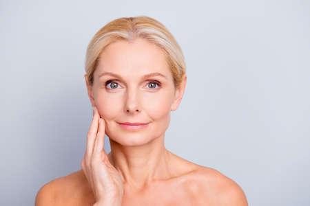Porträt der hübschen, attraktiven, reizend, nackten, nackten Frau, die ihre perfekte Haut, lokalisiert auf grauem Hintergrund berührt