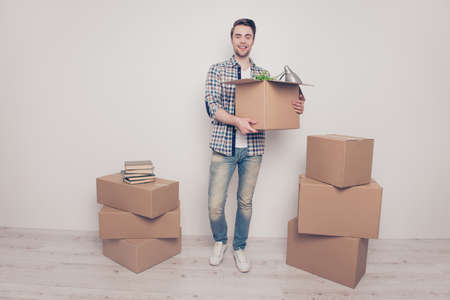 Full-length full-size portrait of glad satisfied rejoicing handsome young man carrying box with staff to the new house