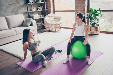 Slim attractive elder thirsty sister holding bottle with liquid sitting with crossed legs, smaller sister relaxing on green fit-ball Banco de Imagens
