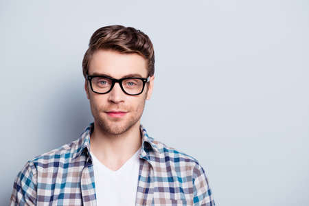 Portrait with copy space of smart, clever guy in glasses  looking at camera over grey background Stock fotó
