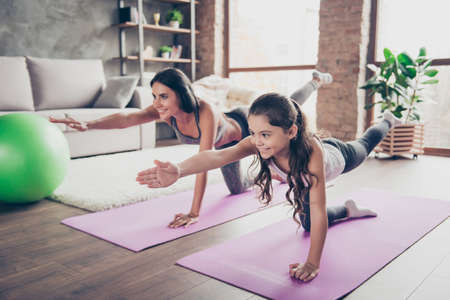 Cute sweet cheerful joyful with long hair schoolgirl and slim sportive mom are doing stretching exercises in room om purple mats