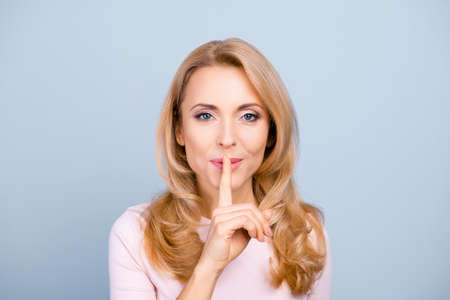 Portrait of pretty, charming, mysterious, sexy, attractive woman holding forefinger on mouth, asking to keep silence