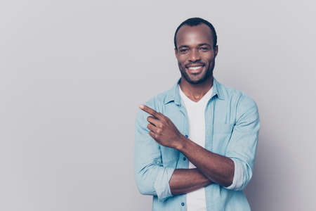 Portrait with empty place of sexy, virile, stunning man in jeans shirt with beaming smile pointing forefinger to copy space, looking at camera, isolated on grey background