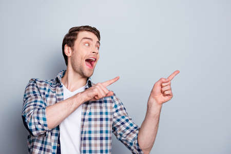 Cheerful, laughing, screaming, shouting, positive, happy man, pointing to copy space, demonstrate new product, solution with index fingers over grey background Stock Photo