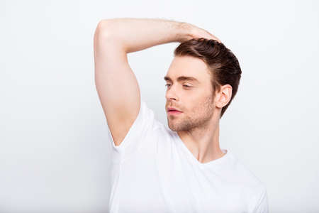 Stunning, perfect, half turned guy in t-shirt looking to the side, holding hand on hair, standing over white background, beauty, hairstyle, haircare and people concept 免版税图像