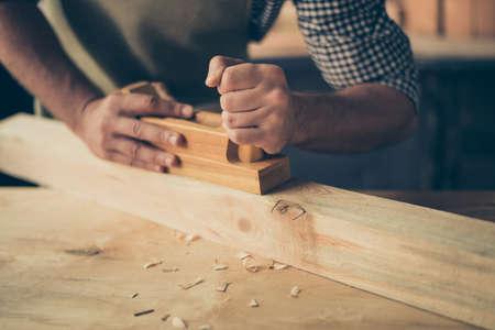 Cropped nah herauf Foto der Hände des Handwerkers, die eine hölzerne Planke glatt und ohne Dornen machen, hält er eine Planke