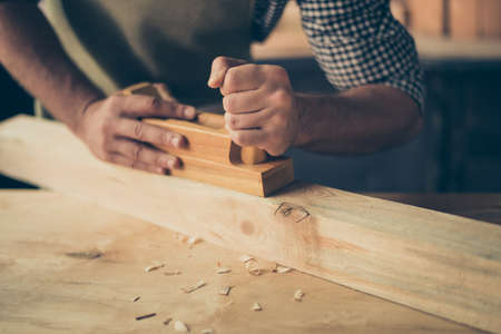 Cropped close up photo of handicraftsman's hands making a wooden plank smooth and without thorns, he is holding a plank