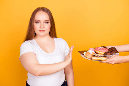 Will-powered woman wearing white tshirt is refusing to consume tasty delicious sweets on a plate, isolated on bright yellow background