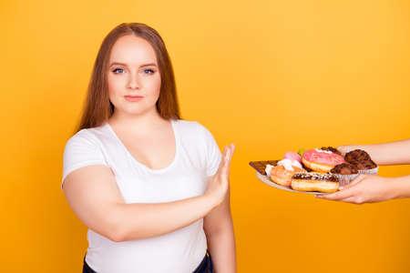 Will-Powered mujer con camiseta blanca se niega a consumir deliciosos dulces deliciosos en un plato, aislado sobre fondo amarillo brillante Foto de archivo - 97559851