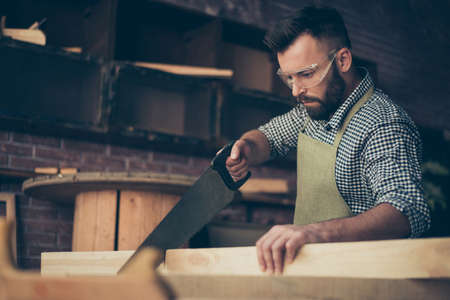 Close up photo of confident handsome bearded skilled wearing apron checkered shirt ans protective glasses carpenter