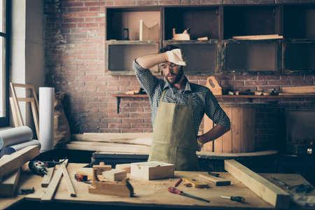 Fatigué épuisé fatigué surmené beau barbu habillé en tablier à carreaux et gants maître de l'artisanat fait à la main essuie la sueur de son front Banque d'images - 97562833