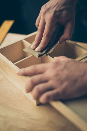 Close up cropped photo of carpenter's hands making smooth the surface on wooden casket using sandpaper he wants to sell his diy Banque d'images - 103868069