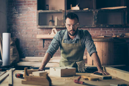 Skilled successful professional quolified pensive confident serious handsome bearded artisan dressed in work clothes is leaning on worktop, he is standing in his workroom