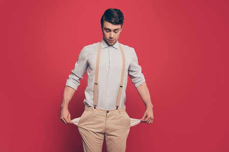 Professionista, mago astuto, illusionista, giocatore d'azzardo in abito casual, mostrando due tasche vuote, in piedi su sfondo rosso, guardando in basso