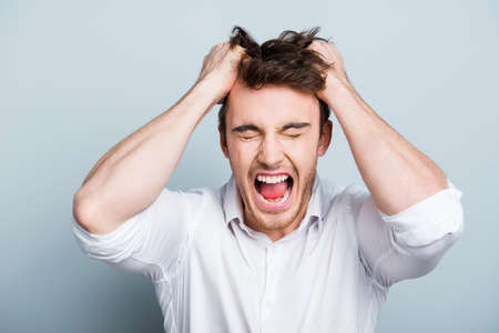 Emotions, stress, madness and people concept - crazy shouting man rending his hair in white shirt, screaming with close eyes and wide open mouth, holding hands on head over gray background Stockfoto